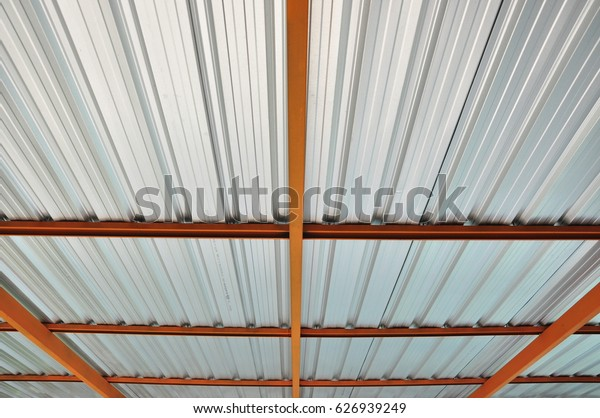 Metal sheet roofing with a orange steel structure.