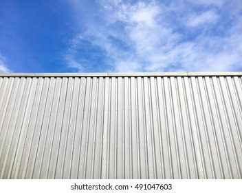 Metal sheet wall and blue sky on sunny day.
