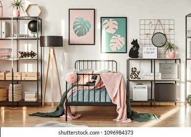 Metal shelves with decorations, botanical posters and comfy bed in a girl bedroom interior