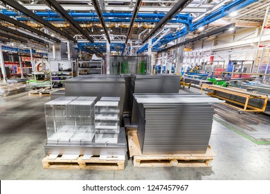 Metal shelves for storage racks. Products of the plant for the production of metal profiles, products stacked. Factory interior.