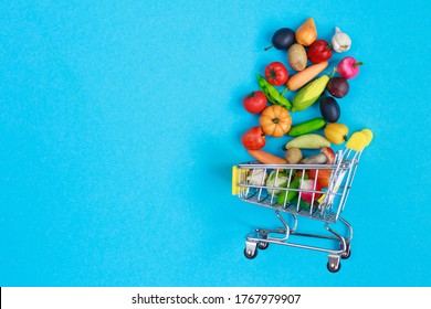 Metal shopping cart with fruits and vegetables on blue background. Toy miniature shopping trolley