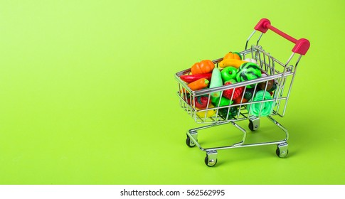 Metal shopping cart with fruits and vegetables on a green background