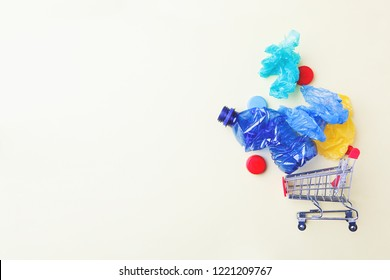metal shopping trolley with plastic waste, environmental concern, plastic waste problem, flat lay, copy space