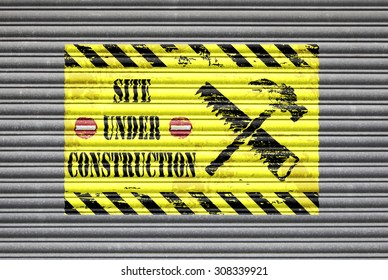 Metal shutter with site under construction painted sign.