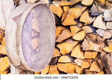 A metal sieve for sifting products hangs on a tree trunk against the background of firewood. Country style