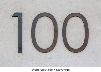 A metal sign for 100 / hundred on a wall in London, UK