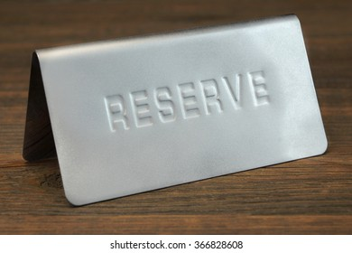 Metal Sign Board Reserve On The Restaurant Wood Table Background, Close Up, Concept Image,