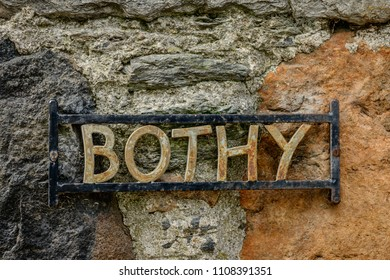 A metal sign for a bothy on a stone wall.