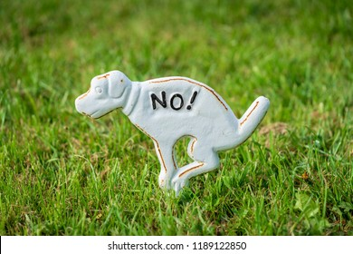 Metal sign of dog placed on the green lawn prohibiting dogs to poop on the grass.