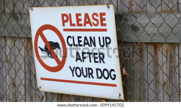 A metal sign hangs on a fence that warns people to clean up after their dog.