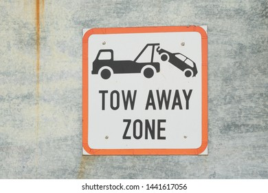 metal sign on galvanised steel sheet with words or text tow away zone in a parking area of an urban or industrial site concept no parking for transport