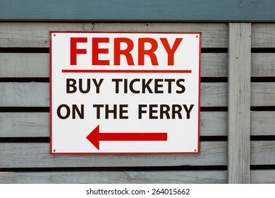 "A metal sign on wood: ""buy tickets on the ferry"" in Whitianga, New Zealand"