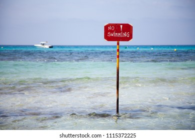 Metal sign prohibiting swimming on a tropical beach