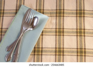 Metal silverware laying on a mint green cloth napkin and coordinated green and tan checked placemat.