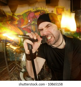 Metal singer cussing into the microphone.  Shot with strobes and slow shutter speed to create lighting atmosphere and blur effects.
