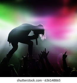Metal singer and fans silhouette in a music concert with colorful light green and pink.
