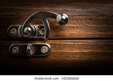 A metal slide clasp lock screwed into the opening of a wooden box.