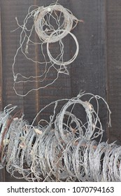 Metal Snares Used By Poachers For Capturing Wild Animals Against A Wooden Fence Background - Image
