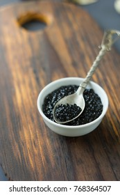 Metal spoon with fresh black caviar over the wooden board.