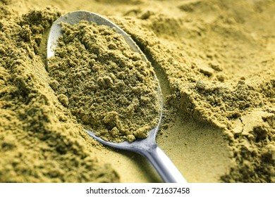 Metal spoon in hemp protein powder, closeup