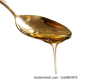 metal spoon with a pouring drop of golden honey isolated on white