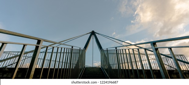 metal stairs lead up to an impressive lookout and viewpoint platform in the Grisons near Flims in Switzerland under a blue sky with white clouds