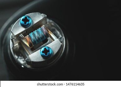 Metal staple staggered fused clapton coil in rebuildable dripping atomizer over dark background