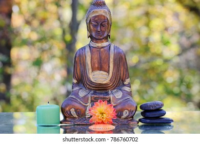 A metal statue of Gautam Buddha with flowers, selective focus.