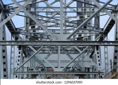 Metal and steel bars, beams and structures of the bridge against blue sky