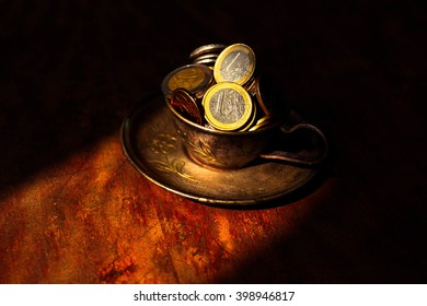 Metal, steel cup and saucer with money euro cent on a dark background old. sunlight