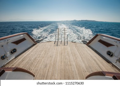 Metal steel ladders on back teak deck of a large luxury motor yacht sailing on a tropical ocean