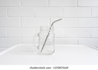 Metal straw in empty glass mug on white table against brick wall background