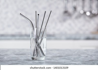 Metal Straws In Transparent Glass Of Water On Kitchen Worktop