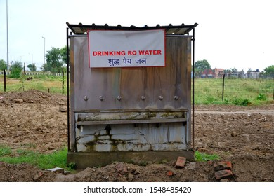 A metal structure in the middle of mud trenches with a sign in English and Hindi about the availability of drinking water. Concept of drinking water wherever and wherever.