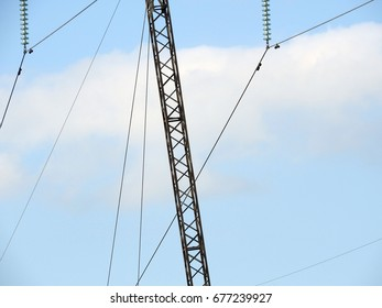 Metal structure with wires of high voltage power lines on blue sky background