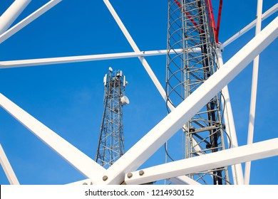 metal structures of cell tower against a blue sky. ladder, support towers and metal construction of telecommunications tower