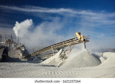 Metal structures of stone crushing equipment at a mining enterprise against a background of white stone dust and clouds against a dark blue sky.