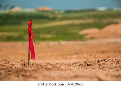 Metal survey peg with red flag on construction site.