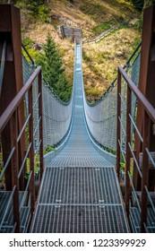 metal suspended bridge in rabby valley on dolomites