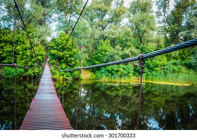 metal suspension bridge over the river made from cables and pipes
