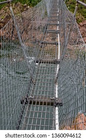 Metal suspension footbridge crossing a river