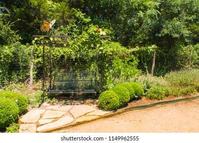 a metal swing in a butterfly garden