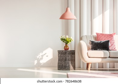 Metal table next to white sofa in bright living room interior with copy space