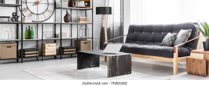 Metal table with silver laptop on grey carpet in man's living room interior with black settee and decorations on shelves