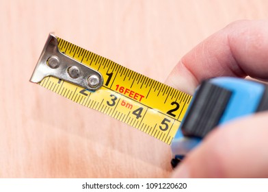 A metal tape measure with divisions in centimeters and feet.