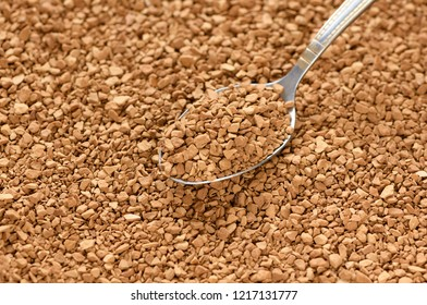 The metal teaspoon with granules of instant coffee is on a brown granulated background.