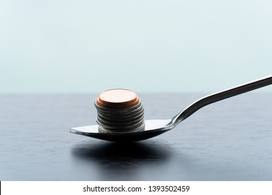 metal teaspoon with silver and bronze coin money for food capitalism business concept financial background