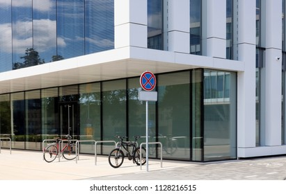 Metal terminals for bicycle parking near a modern no name city office building. Sunny summer day urban concept