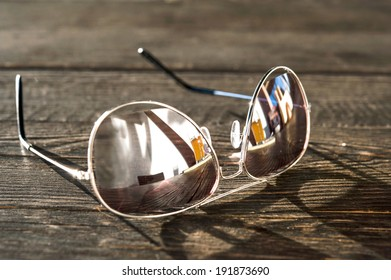Metal thin trendy sunglasses on wooden table. Outdoors closeup.