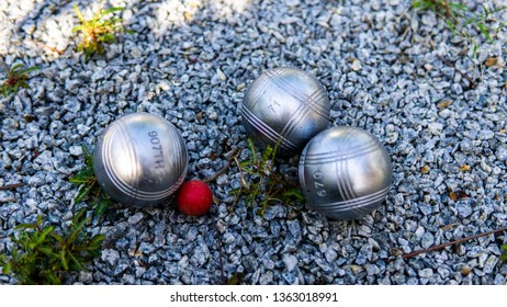 Metal three stripes petanque boules and a red jack on a fine gravel with small green grass at the court.